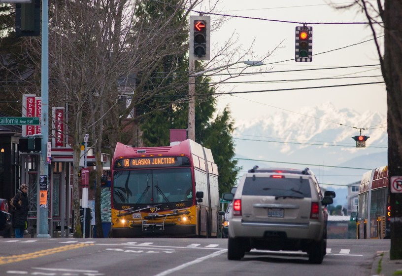 Metro's RapidRide C Line waits at the signal at California Ave in West Seattle with the mountains in the background.