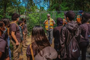 A group of masked youth of all different races and genders surround a few members of the Parks crew as they speak to them about a topic. Parks crew members wear fluorescent orange and yellow vests and work clothes. The group is in the middle of a clearing in a forested area.