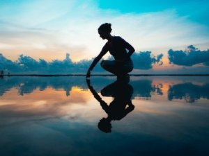 Picture of a woman looking down and touching her reflection
