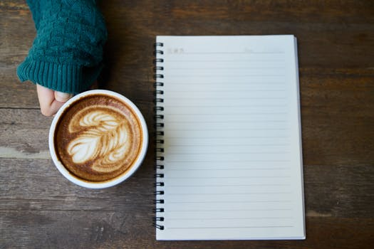 picture of a blank notebook and a cup of coffee on a table