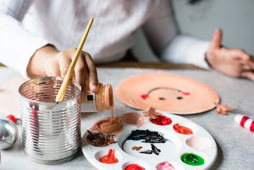 Woman pouring brown paint unto a palette having other paints