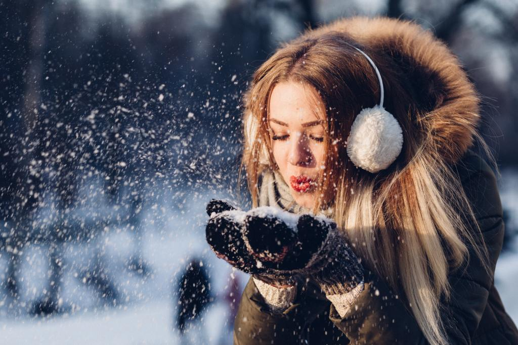 woman standing in the midst of snow in winter