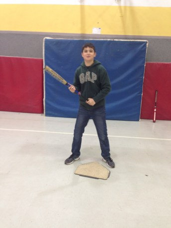 This young man demonstrates the classic Israeli batting stance, hands apart, on home plate, facing the pitcher.