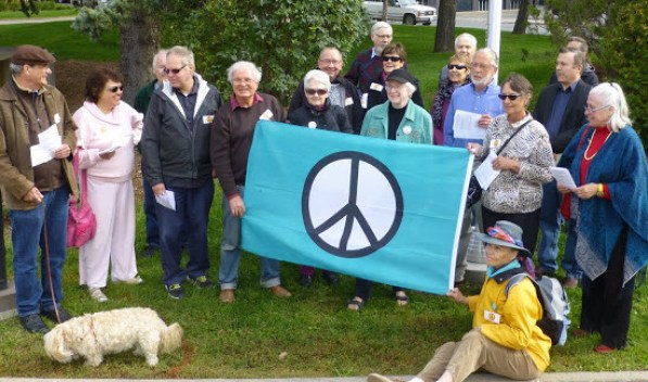 Shows 19 people and a dog surrounding the peace flag.