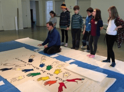 David Melhorn-Boe kneels beside the HUFP banner mid-way through the painting process while students look on.