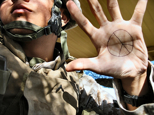 A close up shot of an annonymous, presumably American, soldier in Iraq with a peace symbol drawn on his hand.