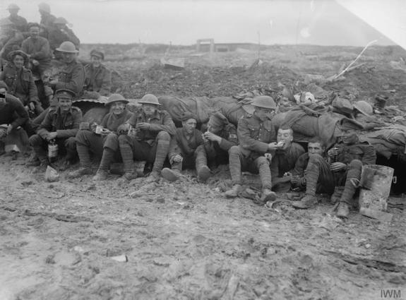Soldiers of the Canadian Expeditionary Force, possibly 25th Battalion (Nova Scotia Rifles) of the 5th Infantry Brigade, 2nd Infantry Division eating rations whilst seated on muddy ground outside a shelter near Pozieres, October 1916, during the final stages of the Battle of the Somme, possibly during the Battle of Le Transloy.