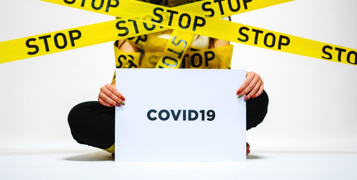 painted female nails holding covid 19 sign