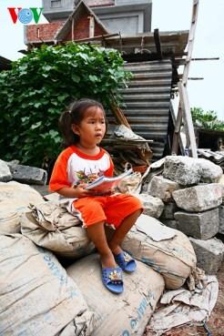 Một em bé ở xã An Vĩnh ngồi chơi trên đống vật liệu xây dựng