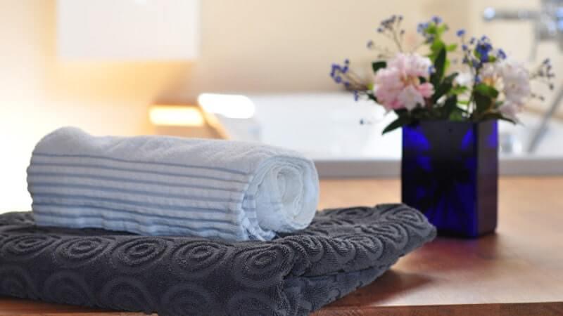 お風呂場に置かれたタオルと花瓶が写った画像