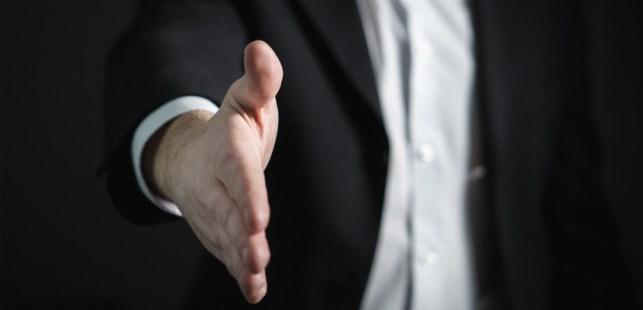 就職が決まって握手するスーツの人