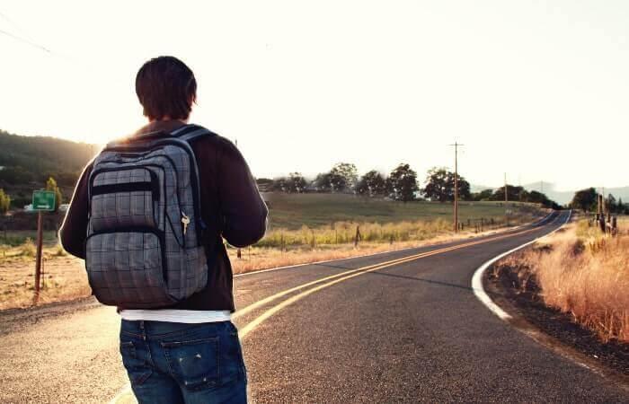 長い道を歩く男性