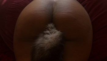 Woman of colour laying face down wearing long grey white tail in her bottom