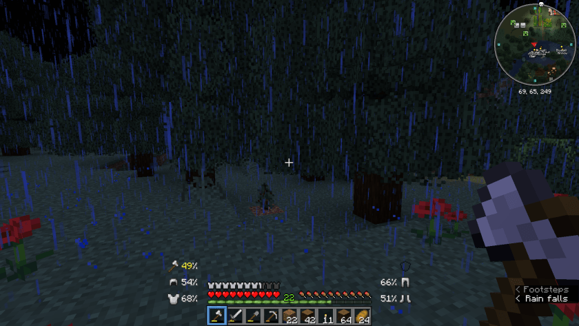 First person view in Minecraft, me holding an axe, and looking at trees through the dark rain of the night.