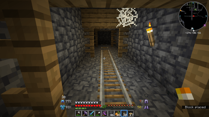 Tunnel with a spiderweb in the corner, rail leading further into the darkness