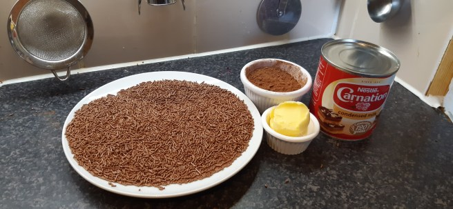 Plate with chocolate strands, ramekins containing cocoa and butter and a tin of condensed milk, on a granite effect background. There are kitchen utensils hung on a tiled wall in the backgrround.