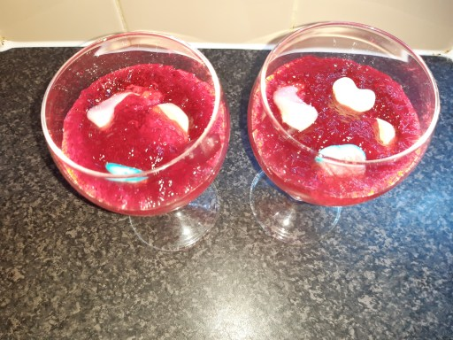 Glasses containing raspberry jelly and sweets on a granite effect worktop.