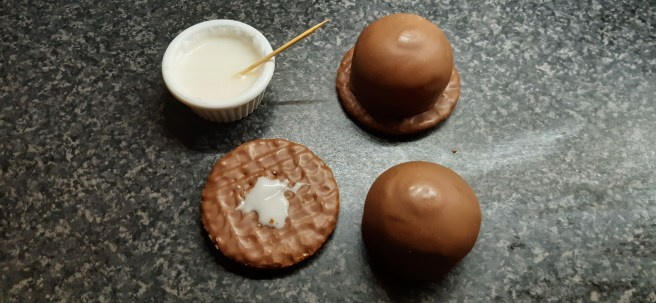 Chocolate marshmallows on chocolate biscuits on a black work surface. There is a pot of white glace icing with a cocktail stick sticking out.