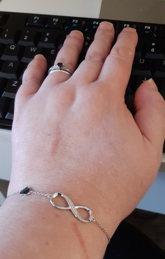 A photograph of my silver and sapphire wedding rings from my husband and eternity bracelet from my poly partner
