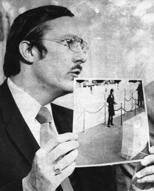 Prokurator James Browning pokazujący zdjęcia znapadu nabank
