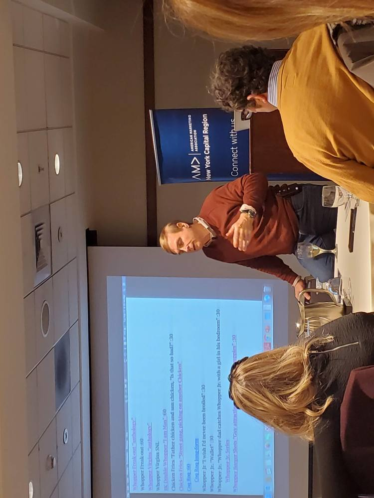 Photo of Russ Klien, former CMO at Burger King speaking in front of a powerpoint presentation at the American Marketing Association Executive Networking event in February 2020