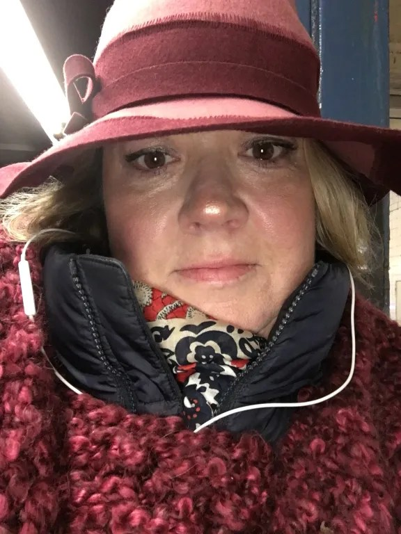 the Author waiting for the subway train & enjoying a top podcast