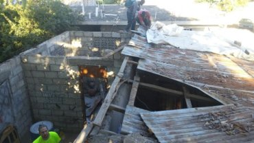 Taking off the old, damaged roof, in the shade of large mango tree