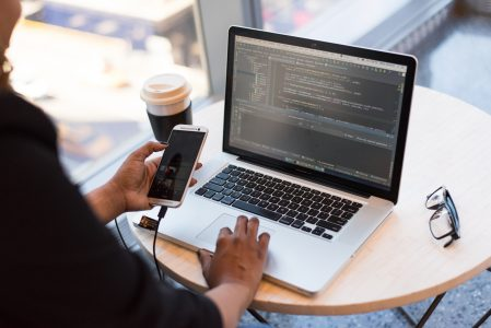 Woman with coffee working on phone plugged into laptop