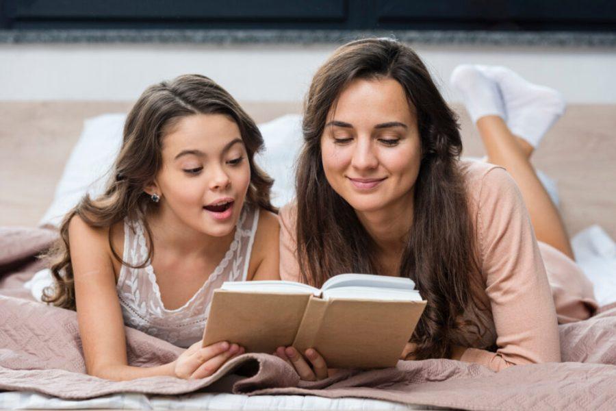 Äiti ja tytär lukevat yhdessä kirjaa.