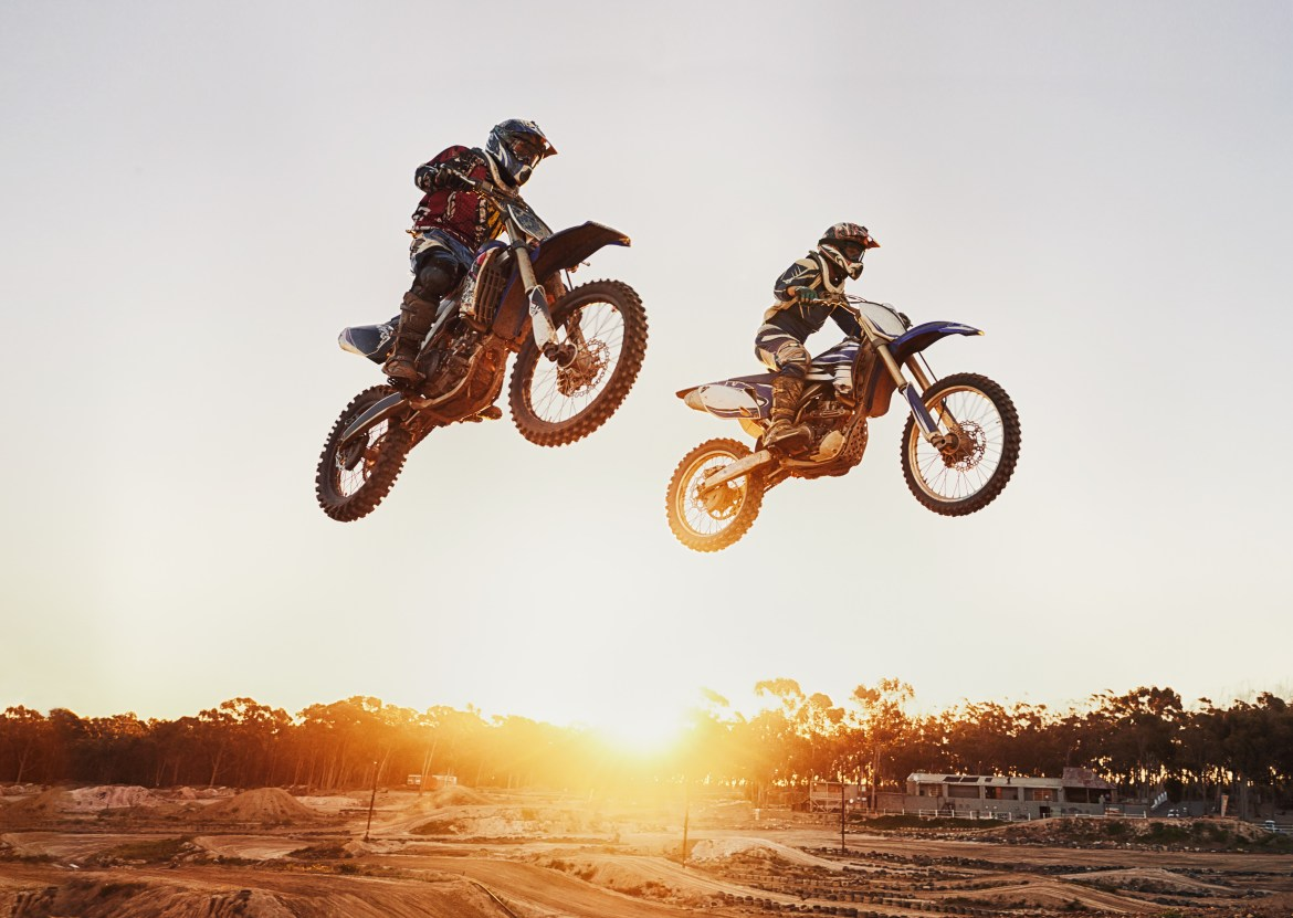 two airborne motorbikes in front of a sunrise