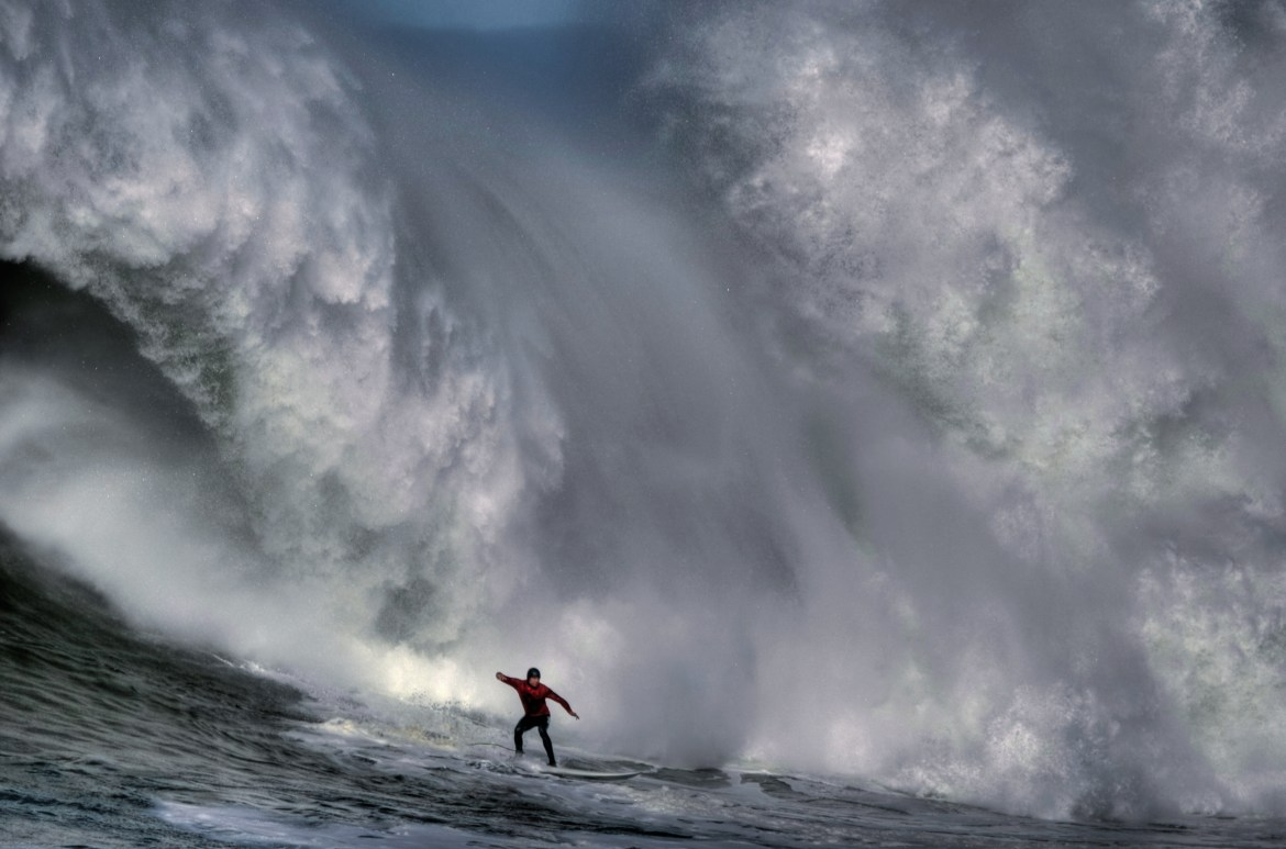 surfer at the bottom of a huge wave