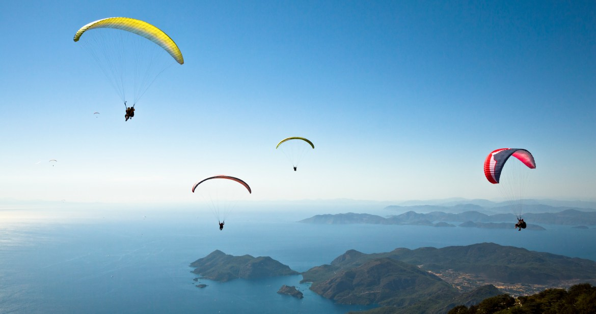 people at different heights parachuting to a island