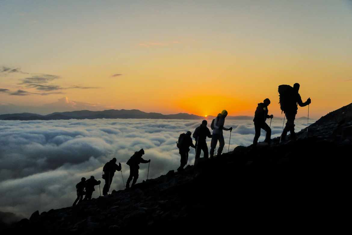 hikers walking up a mountain during sunset