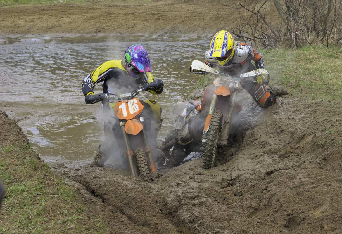 two motocross bikers stuck in the mud on a narrow path