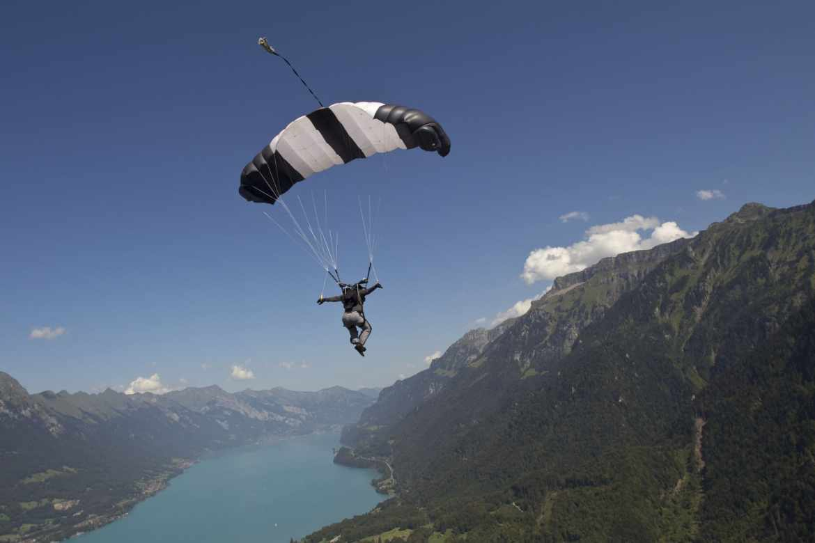 man paragliding near a mountain and river