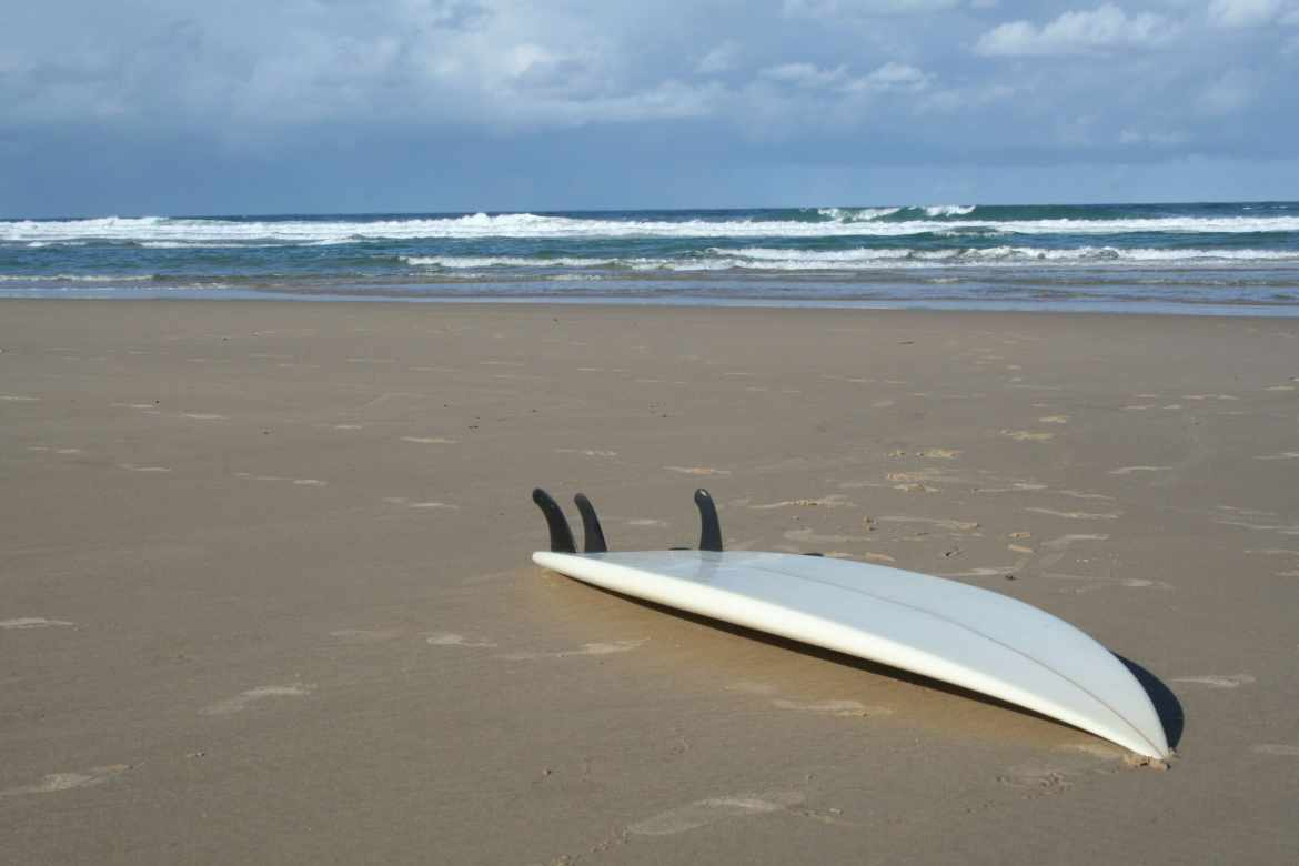 abandoned surfboard next to the ocean