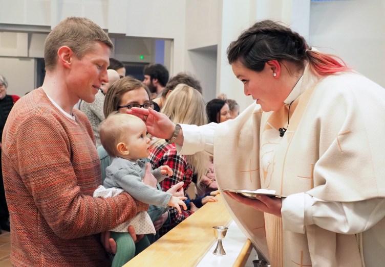 Pappi siunaa vanhempiensa kanssa alttarilla olevan pienokaisen.