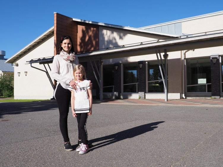Äiti ja lapsi seisovat vierekkäin koulun pihassa.
