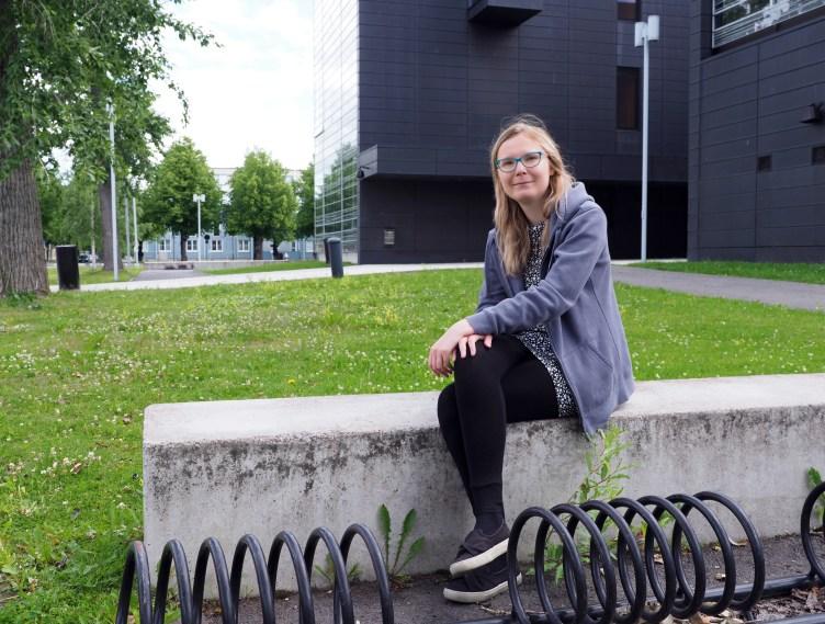 Nuorisotyönojaaja istuu koulun pyöräparkin luona.