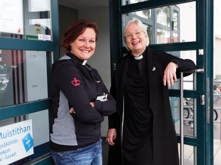 Oppilaitospapit Sanna Kauppinen ja Tiina Belov hymyilevät Riveria Peltolan ovella.