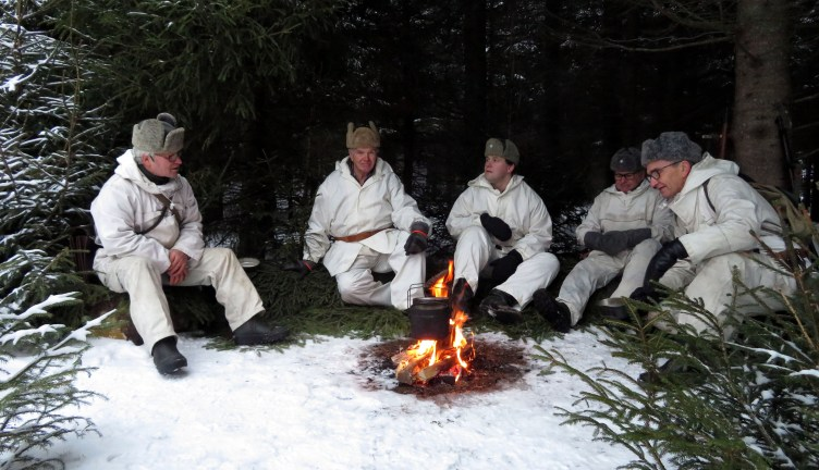 Sotilaita esittävät näyttelijät istuvat nuotion ääressä.