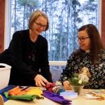 Lastenohjaaja ja pastori valmistelevat askarteluja pöydän ääressä. Pöydällä on papereita, saksia ja muita askartelutarvikkeita.