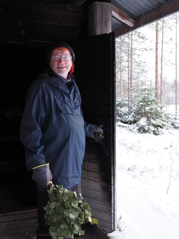 Seppo Siltavuori seisoo hymyilemässä savusaunan ovella vihta kädessä.