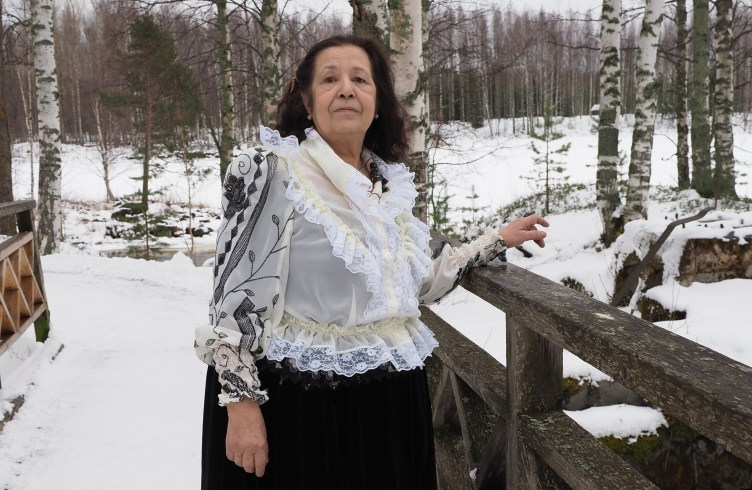 Sita Nyman seisoo ulkona sillalla talvimaisemassa.