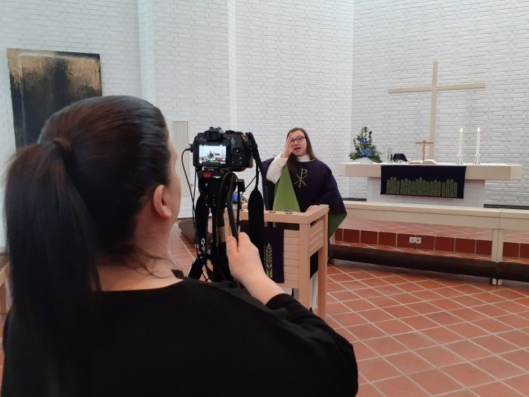 Kuvaaja kuvaa videokameralla alttarilla lukupulpetin edessä ristinmerkkiä tekevää pastori Erika Kyytsöstä.