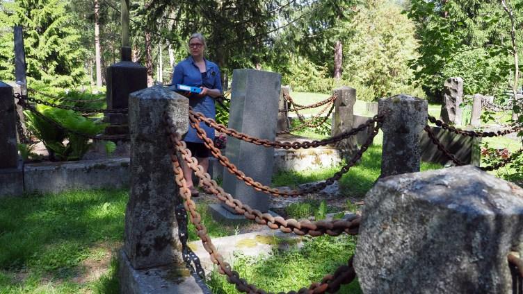 Hautaustoimen päällikkö Virpi Kiviniemi seisoo kallistuneen hautamuistomerkin vieressä.
