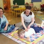Lastenohjaaja hieroo viltillä makaavan lapsensa selkää. Varhaiskasvatuksen ohjaaja istuu lattialla heidän vieressään.
