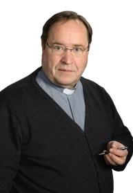 kirkkoherra Ari Autio katsoo kameraan kynä kädessään