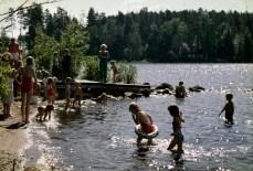 Lapsia ja aikuisia uimassa Männikköniemen rannalla.