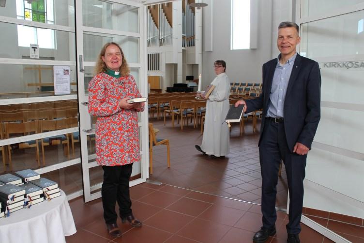 Leena Mgaya ja Pekka Auvinen seisovat Noljakan kirkkosalin ovella, Emilia Heikkinen kävelee kirkkosalissa alba päällä ja kynttilä kädessä.